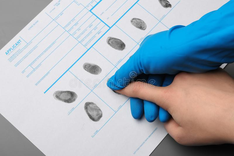 Investigador que toma huellas dactilares del sospechoso en la tabla Experiencia criminal fotos de archivo libres de regalías