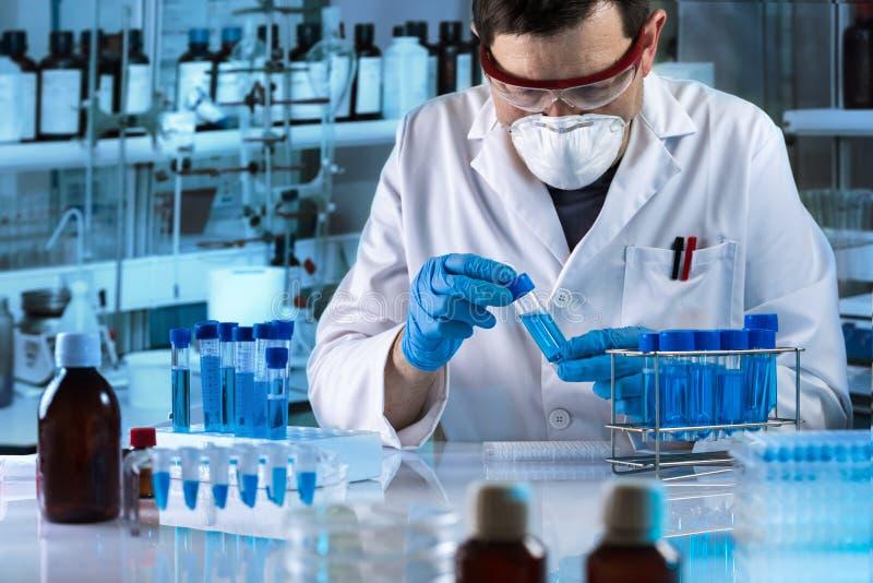 Investigador que trabaja con la muestra de líquido azul en el tubo para el análisis en el laboratorio de ciencia imagenes de archivo