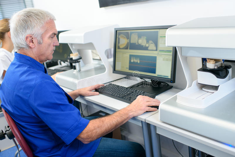 Investigador serio que mira la pantalla de ordenador en laboratorio imagen de archivo libre de regalías