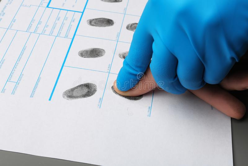 Investigateur prenant des empreintes digitales de suspect à la table Expertise criminelle image stock