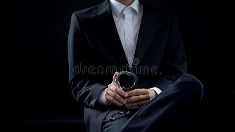 Investigateur tenant des menottes dans des mains, pénalité criminelle, justice d'ordre public photos stock