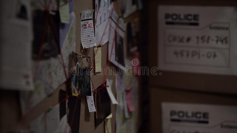 Investigation board with pinned photos, newspapers and notes, solving crime stock image