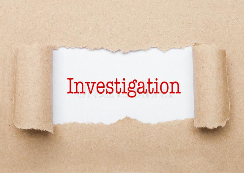 Investigation text appearing behind brown paper stock photos