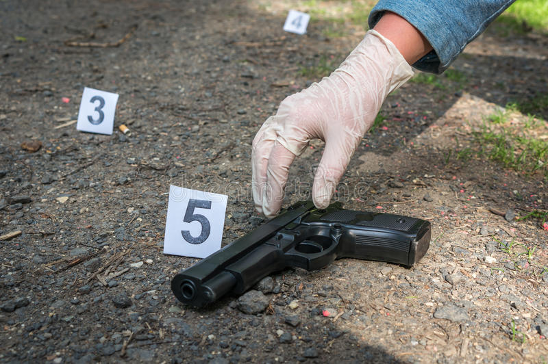Investigator collects evidence - crime scene investigation. Investigator collects evidence pistol - crime scene investigation stock photo