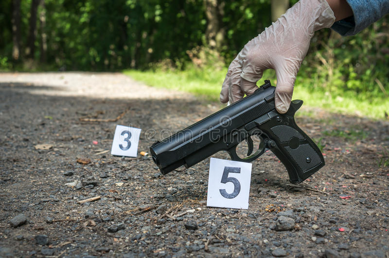 Investigator collects evidence - crime scene investigation. Investigator collects evidence pistol - crime scene investigation royalty free stock photo