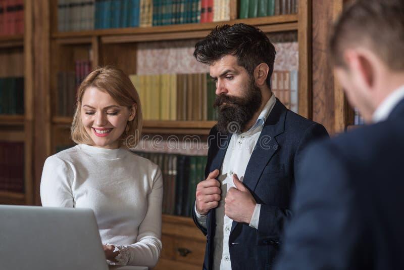 Investigue el concepto Hombres de negocios del uso de las informáticas para hacer la investigación Trabajo de los estudiantes uni imágenes de archivo libres de regalías