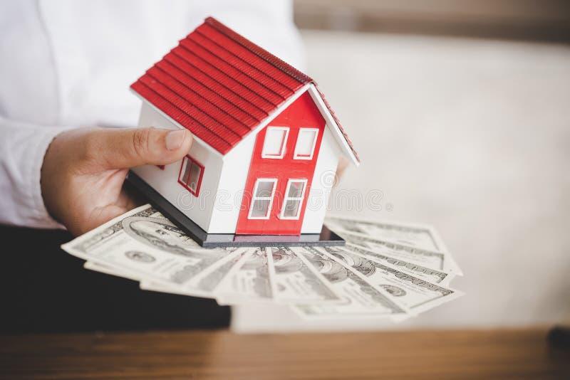 investimento, bens imobili?rios e conceito da propriedade - fim acima do modelo da casa no dinheiro do d?lar imagem de stock