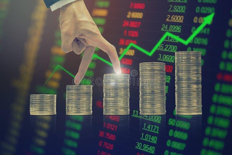 Investimento a brilhar, Mão do empresário a subir nas moedas com flecha verde e antecedentes é o preço das ações foto de stock