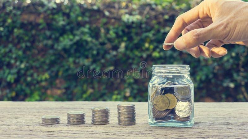 Investimento dei soldi o concetti di risparmio Una mano dell'uomo che mette moneta nel barattolo di vetro sulla tavola di legno immagine stock