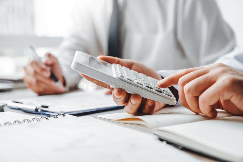 investimento detrabalho de Team Accounting do negócio e custo de salvamento que discutem dados financeiros do gráfico do plano no fotos de stock