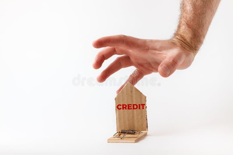 Investimentos bancários e riscos a mão de um homem alcança uma ratoeira com uma casa esquemática de papelão, com a inscrição CRED imagens de stock royalty free