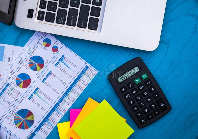 Investing motivational finance budget concept with charts and graphs and calculator on wooden board. Investment Strategy motivational finance budget concept with royalty free stock photos