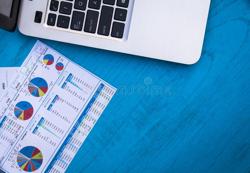 Investing motivational finance budget concept with charts and graphs and calculator on wooden board. Investment Strategy motivational finance budget concept with royalty free stock photo