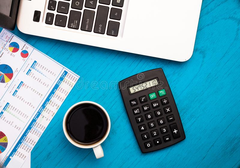 Investing motivational finance budget concept with charts and graphs and calculator on wooden board. Investment Strategy motivational finance budget concept with stock photo