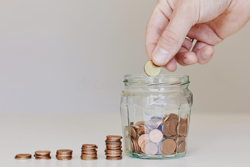Investing, saving money or growing business concept. Male hand putting money coin in the glass jar stock photos