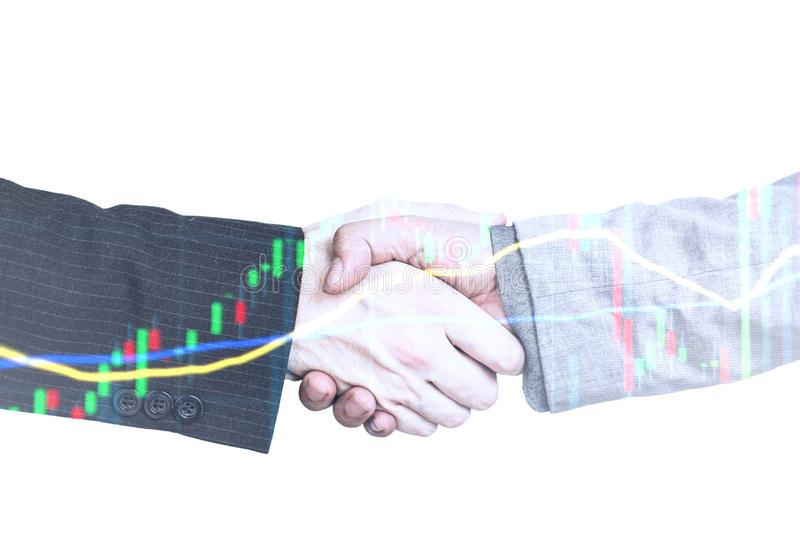 Handshake Investing and stock market concept gain and profits with faded candlestick charts. stock photo