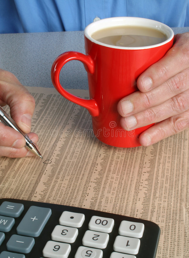Investing in stocks and shares. Man holding cup of coffee whilst selecting shares from newspaper stock photography