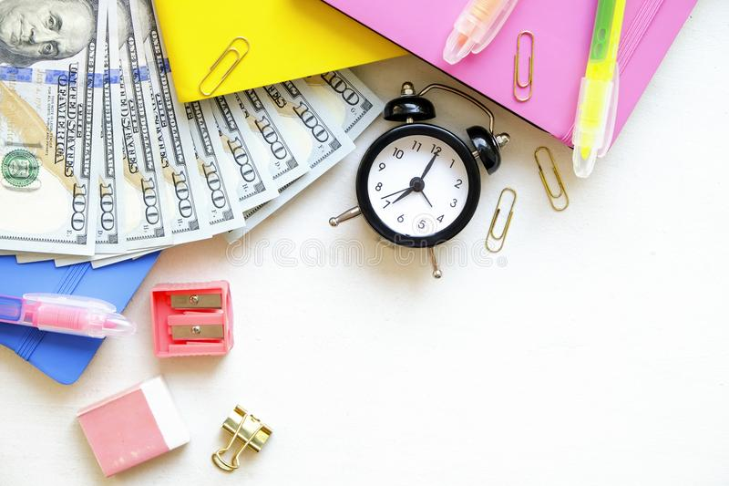 Investing time and money into education concept. Different school supplies, banknotes. Top view, close up. royalty free stock photo