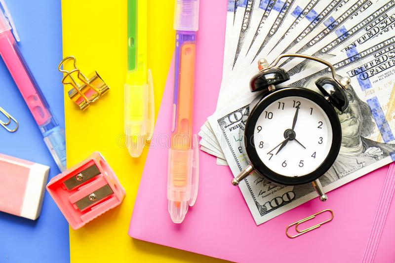 Investing time and money into education concept. Different school supplies, banknotes. Top view, close up. royalty free stock image