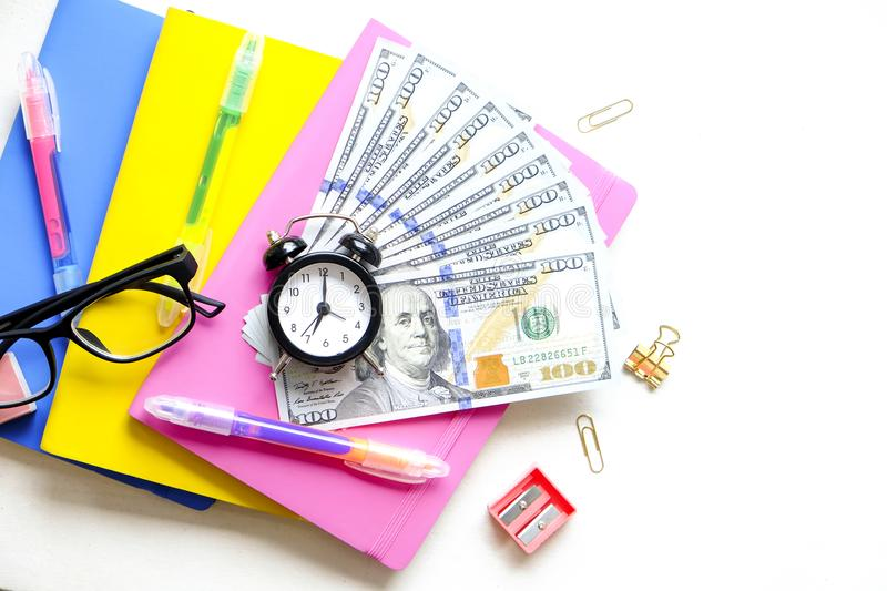 Investing time and money into education concept. Different school supplies, banknotes. Top view, close up. royalty free stock images