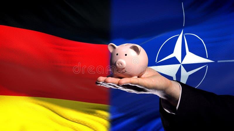 Investissement de l'Allemagne dans l'OTAN, tirelire de participation de main d'homme d'affaires, fond de drapeau photographie stock libre de droits