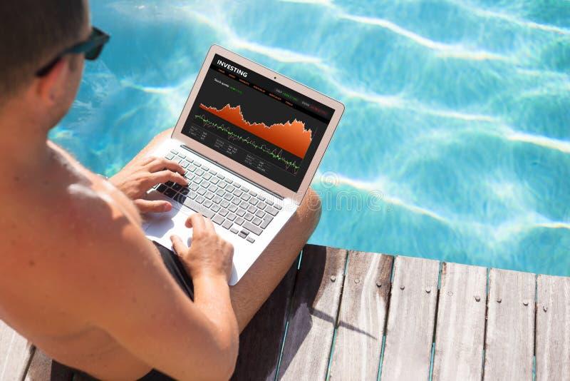 Investisseur regardant des cotes sur l'ordinateur portable par la piscine photographie stock