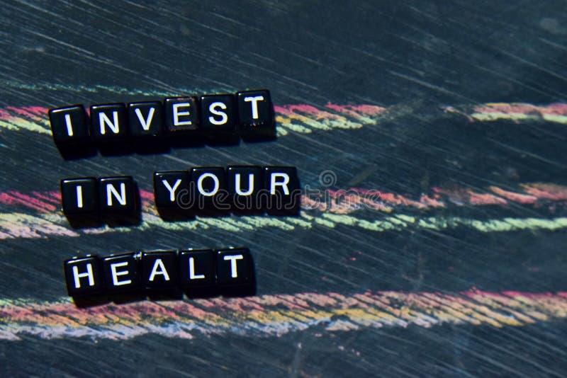 Investissez dans votre santé sur les blocs en bois Image traitée croisée avec le fond de tableau noir images stock