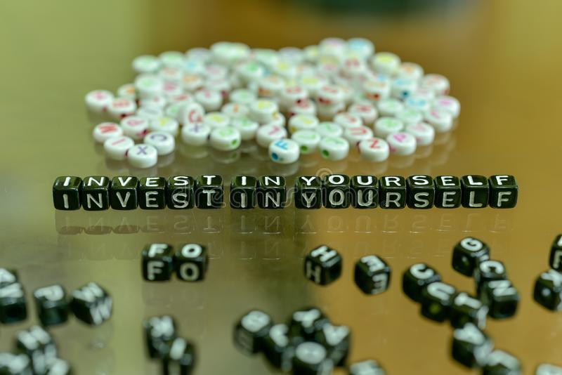 INVESTISSEZ DANS VOUS-MÊME écrit avec le cube noir acrylique avec les perles blanches d'alphabet sur le fond en verre image stock