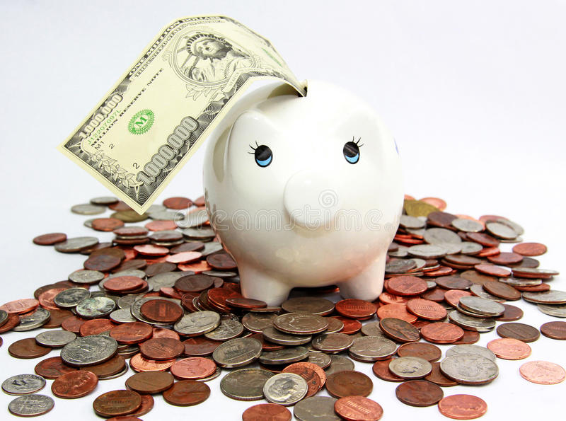 Investment. White ceramic piggy bank with a million dollar bill on the slot and stepping on US coins. A concept of prosperity and investment royalty free stock photos
