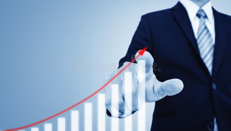 Investment and business growth concept. Businessman pointing on increasing financial graph stock photography