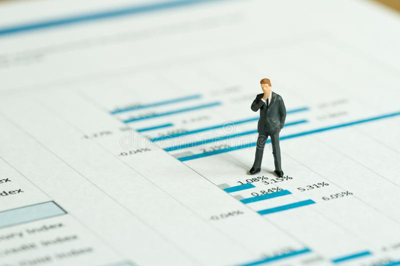 Investment, financial performance report analysis concept, miniature people figurine success businessman standing and thinking on. Printed stock exchange data stock photo