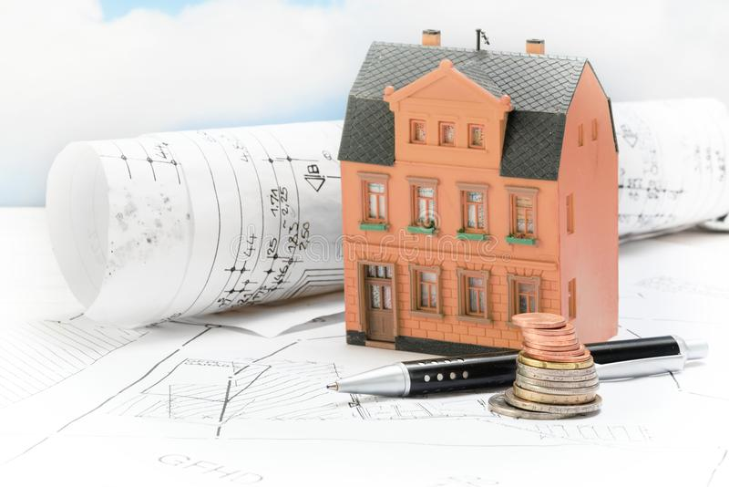 Investment in old building renovation, model house with architectural plans, coins and pen, real estate concept with copy space royalty free stock image