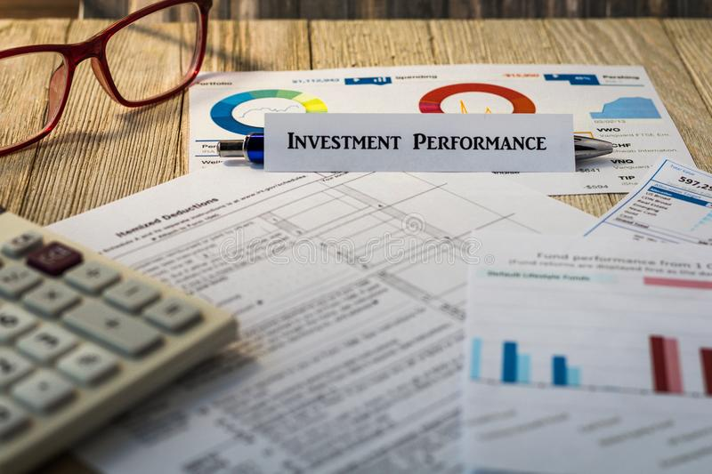 Investment Performance financial strategy motivational concept. Investment Performance motivational concept with charts and graphs on wooden board royalty free stock image