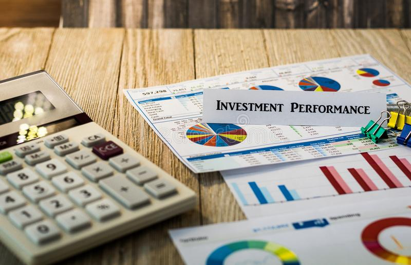 Investment Performance financial strategy motivational concept. Investment Performance motivational concept with charts and graphs and calculator on wooden board royalty free stock image