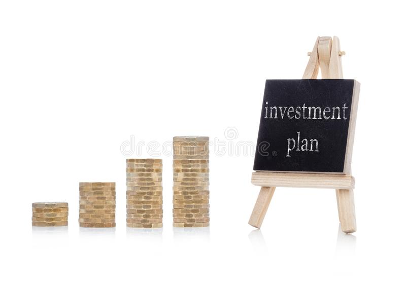 Investment plan concept text on chalkboard. With coins on white background stock photos