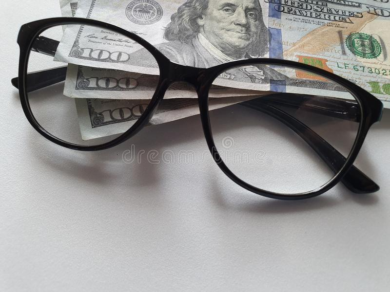 Investment and promotion for a better vision, American banknotes of 100 dollars and black plastic frame glasses. Accessory, closeup, view, offer, promotion stock photography