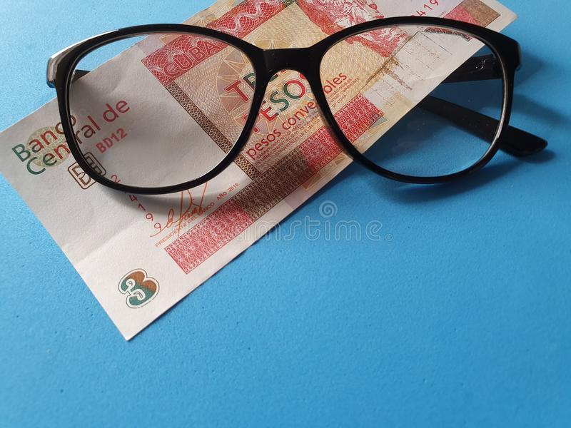 investment and promotion for a better vision, Cuban banknote of three pesos and black plastic frame glasses stock photography