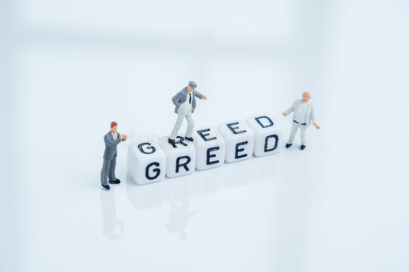 Investment psychology greed and fear in stock market or money game and financial asset, miniature businessmen standing with cube. Block building the word Greed royalty free stock photo