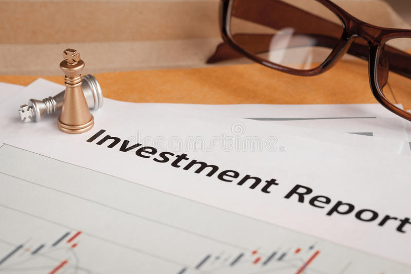 Investment Report letter document and eyeglass; document is mock. Up stock image
