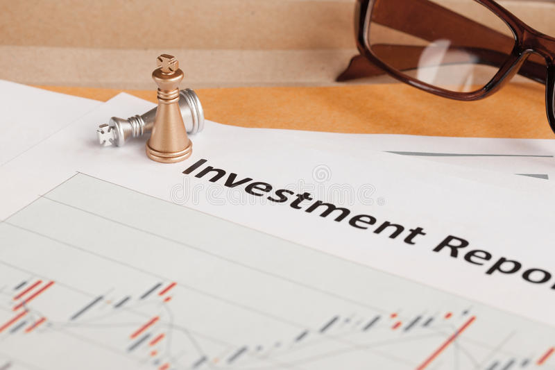 Investment Report letter document and eyeglass; document is mock. Up royalty free stock photos