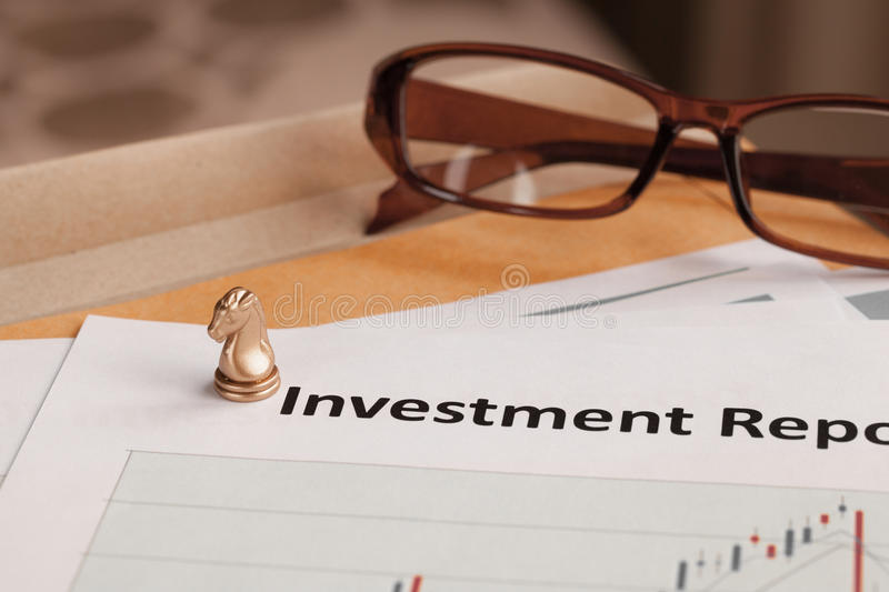 Investment Report letter document and eyeglass. Document is mock-up royalty free stock image