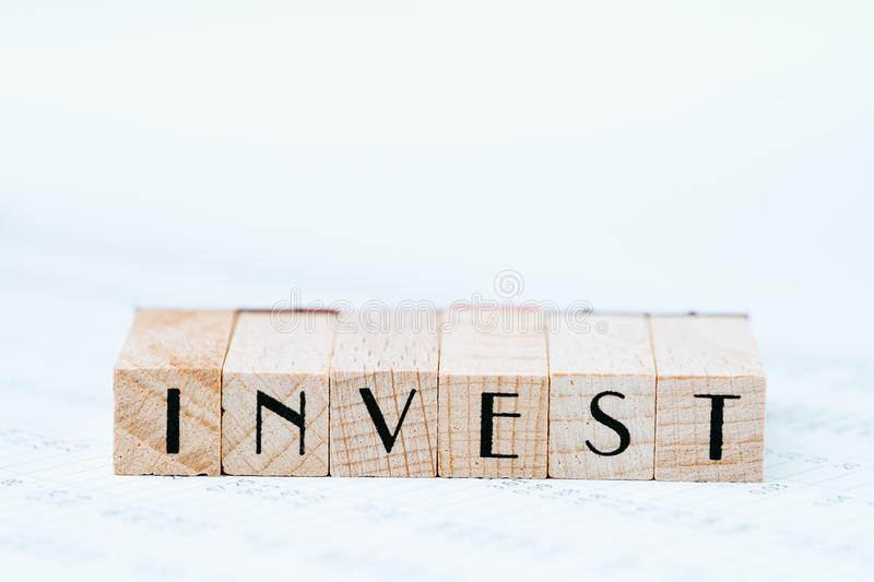 Investment, stock, bond or equity  concept, pen and wooden stamp block arrange the word INVEST on asset price numbers table report royalty free stock images