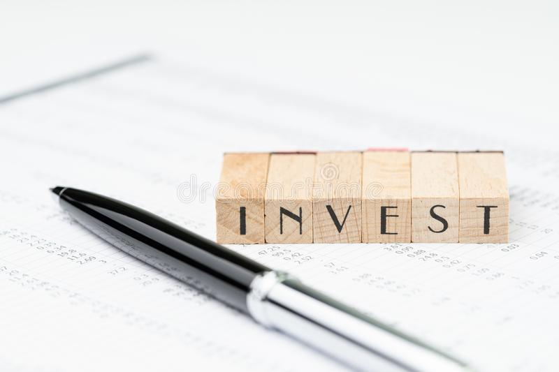 Investment, stock, bond or equity concept, pen and wooden stamp. Block arrange the word INVEST on asset price numbers table report paper on table stock photography
