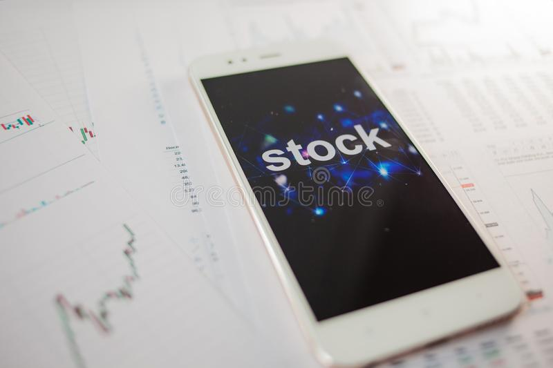 Investment in stocks, concept. Reports and statistics, analysis of the securities market. Smartphone with an inscription on the screen royalty free stock photography