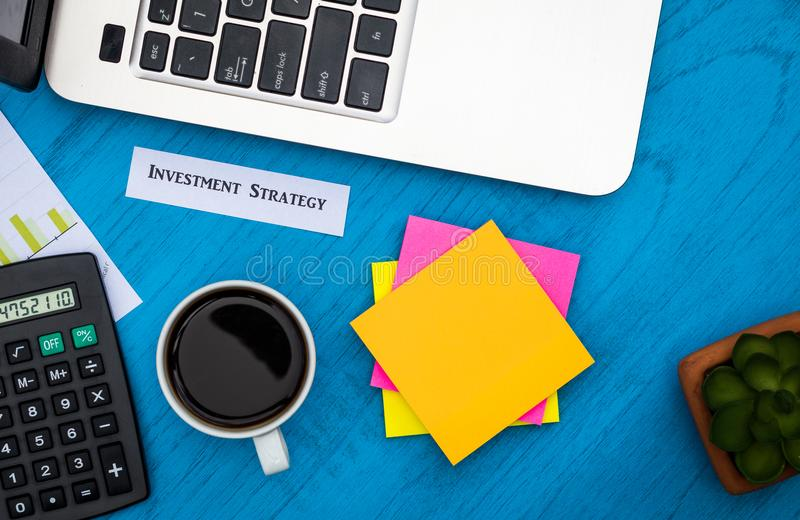 Investment Strategy concept with charts and graphs and calculator on wooden board. Investment Strategy motivational finance budget concept with charts and graphs stock image