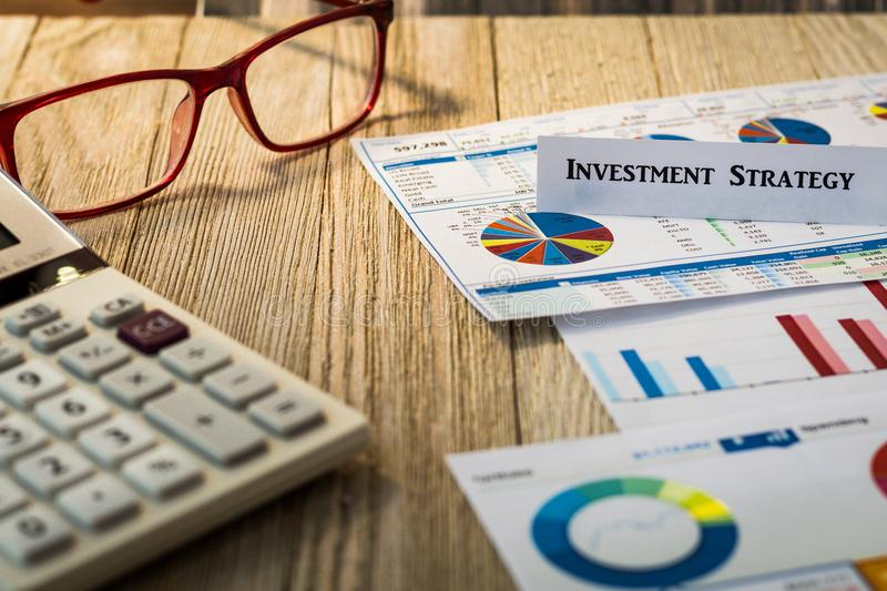 Investment Strategy motivational concept. With charts and graphs and calculator on wooden board royalty free stock photo