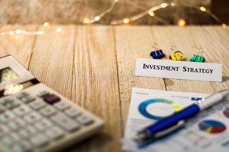 Investment Strategy motivational concept. With charts and graphs and calculator on wooden board and festive lights stock photography