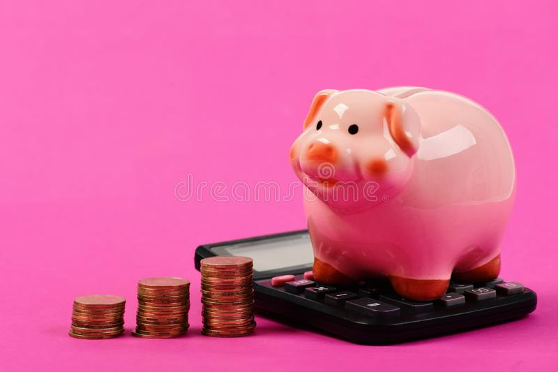 Investments and income growth idea. Budget and tax payments concept. Piggy bank stands next to stacks of coins and calculator. Ceramic toy pig with money stock photos