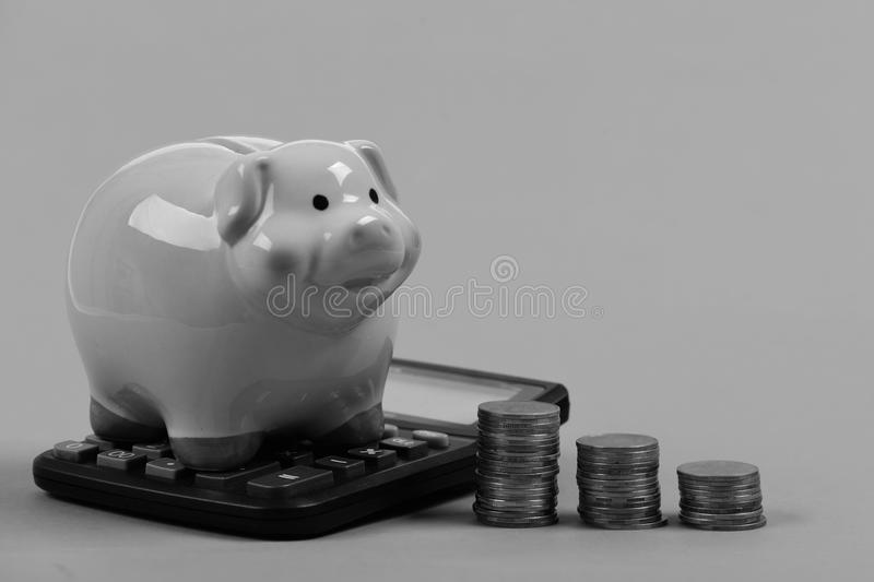 Investments and income growth idea. Budget and tax payments concept. Piggy bank stands next to stacks of coins and calculator. Ceramic toy pig with money stock photo