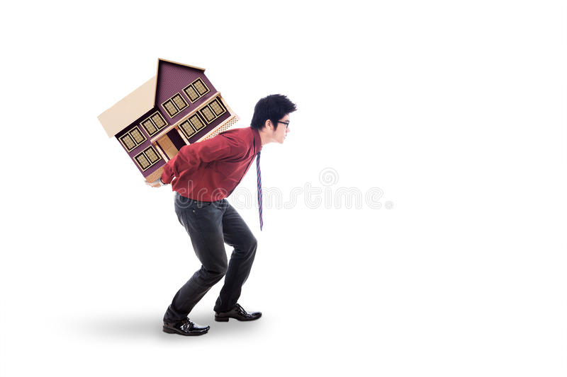 Investor carrying house model in the studio. Image of young male entrepreneur walking in the studio while carrying house model. isolated on white background royalty free stock image